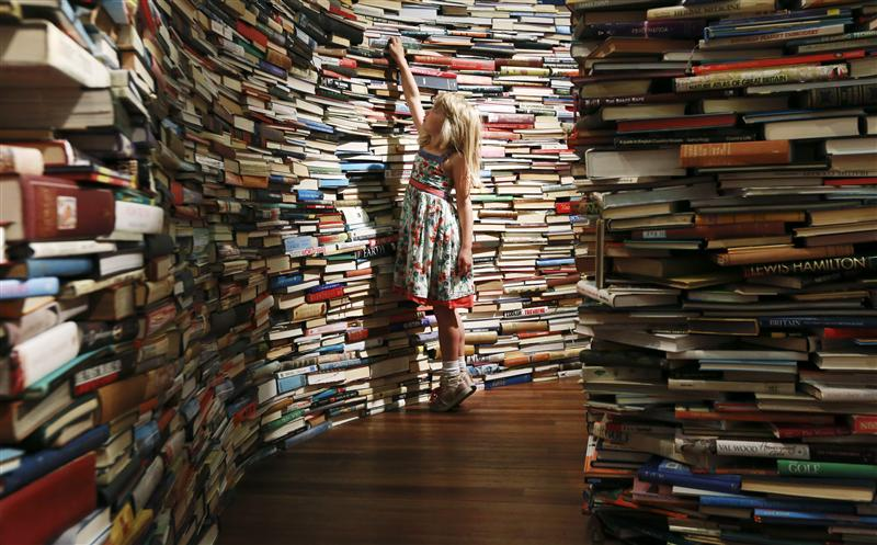 "Leona, 7, poses inside a labyrinth installation made up of 250,000 books titled ""aMAZEme"" at the Royal Festival Hall in central London"