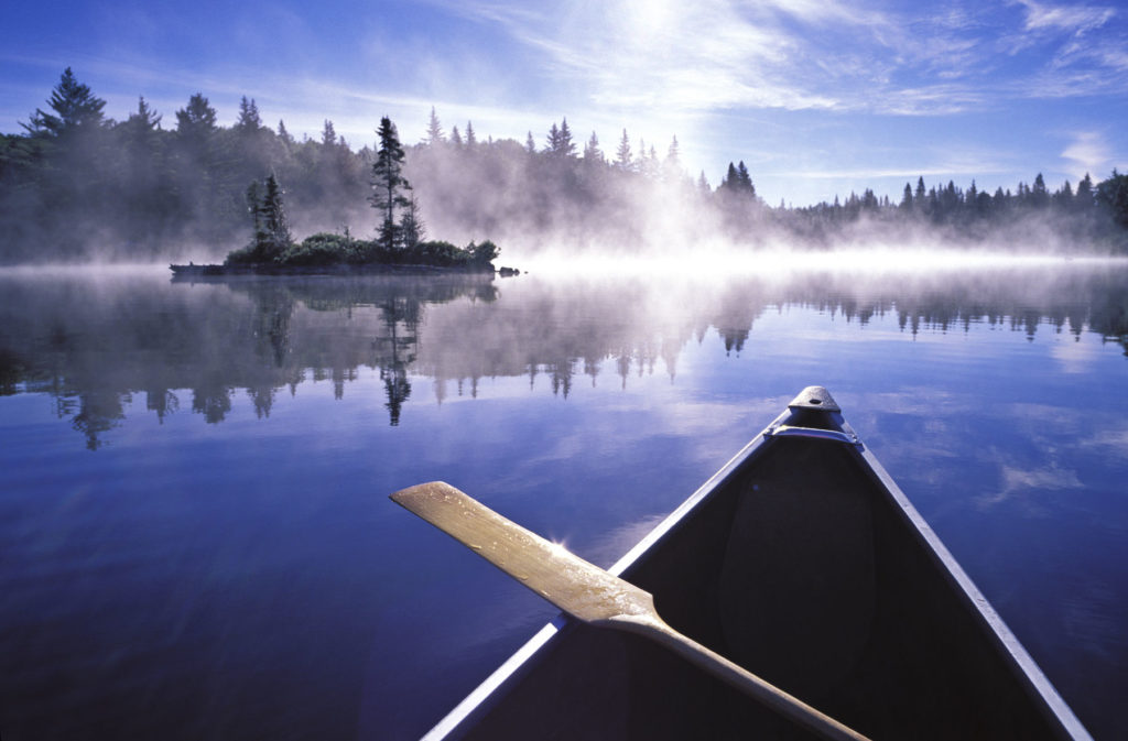 Canada, Ontario, Algonquin Provincial Park, canoe and mist at sunrise on Little Doe Lake.
